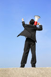 Business man using megaphone. Happy business man using megaphone shouting with blue sky background, asian Royalty Free Stock Image