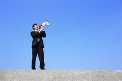Business man using megaphone. Happy business man using megaphone shouting with blue sky background, asian Stock Photography