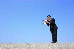Business man using megaphone. Happy business man using megaphone shouting with blue sky background, asian Stock Photo