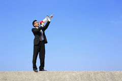 Business man using megaphone. Happy business man using megaphone shouting with blue sky background, asian Royalty Free Stock Photo