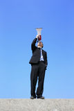 Business man using megaphone. Happy business man using megaphone shouting with blue sky background, asian Royalty Free Stock Photos