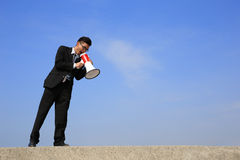 Business man using megaphone. Happy business man using megaphone shouting with blue sky background, asian Stock Images