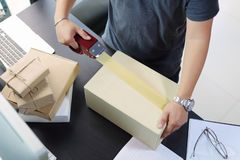 Business man using Metal Tape Dispenser and packing a parcel box on black desk in home office .selective focus.product packaging. And online business shipping stock image