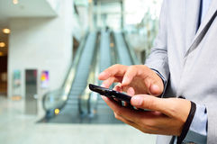Business Man Using Mobile while going down Escalator. Business Man Using Mobile Phone while going down Escalator Royalty Free Stock Photos