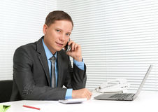 Business man using mobile phone. Cheerful young business man using mobile phone at desk Royalty Free Stock Photo