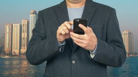 Business man using mobile phone on background modern skyscrapers. Business man using mobile phone for browsing news in internet on background modern skyscrapers stock video footage