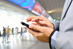 Business Man using Mobile Phone in Modern Train Station. Or Subway station Royalty Free Stock Photo