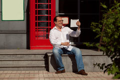Business man using mobile phone red classic English telephone bo Royalty Free Stock Images