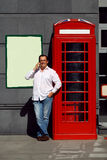 Business man using mobile phone red classic English telephone bo Stock Image