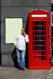 Business man using mobile phone red classic English telephone bo Royalty Free Stock Photography