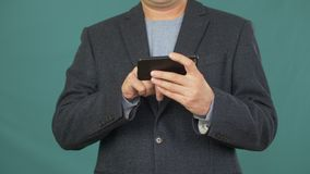 Business man using mobile phone screen on green background. Adult man touching screen smartphone for browsing photos and images in social networks stock video footage