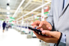 Business Man using mobile phone while shopping in supermarket. Business Man using mobile phone while shopping in supermarket as Telecommunication concept Stock Image