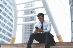 Business man using mobile phone sitting outdoor royalty free stock photography