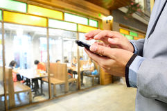 Business man using mobile smart phone in Restaurant or Food Cour Royalty Free Stock Photos