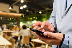 Business man using mobile smart phone in Restaurant or Food Cour Royalty Free Stock Images