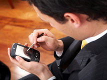 Business man using a pda Stock Images