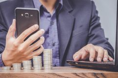 Business man using smart phone and laptop with money coin stock photo