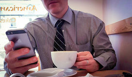 Business man using smart phone to work through lunch break. Smart suited business man on lunch break coffee iPhone communication Royalty Free Stock Images