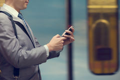Business man using smart phone at train station. Business people hand using smart phone in subway station, train passing by at the background Stock Photo