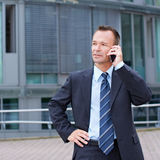 Business man using smartphone. Busy business man using his smartphone to make a phone call Royalty Free Stock Image