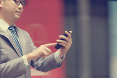 Business man using smartphone at train station. Asian business man hand using smart phone in subway station, train passing by at the background Royalty Free Stock Images