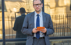 Business man using tablet PC in orange cover on a city street. Royalty Free Stock Photography