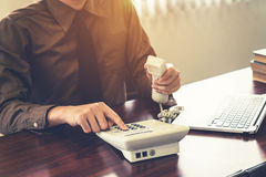 Business man using telephone and laptop in the office. Vintage t Stock Image