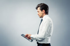 Business man with touchpad. Business man using a touchpad grey background Royalty Free Stock Photos