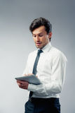 Business man with touchpad. Business man using a touchpad grey background Royalty Free Stock Photo