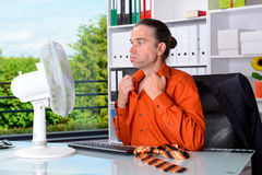 Business man with ventilator at his desk in summerly hot office Stock Photos