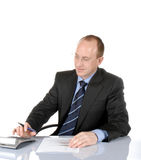 Business man VI. Isolated business man sitting behind a desk and typing on a calculator royalty free stock photos