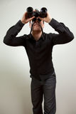 Business man with a vision. Young man wearing black shirt and holding binoculars, isolated on white Royalty Free Stock Photography