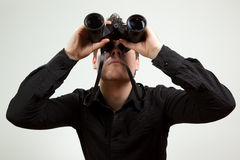 Business man with a vision. Young man wearing black shirt and holding binoculars, isolated on white stock images