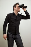 Business man with a vision. Young man wearing black shirt and holding binoculars, isolated on white stock photography