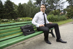 Business man waiting. Young businessman sitting on a bench outdoors. It looks like he is waiting for someone stock photo