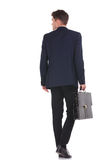 Business man walking while holding his briefcase. Stock Photography