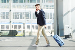 Business man walking with luggage on telephone call at station Stock Images