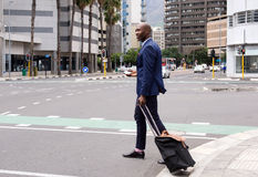 Business man walking with pull bag in the city Royalty Free Stock Image