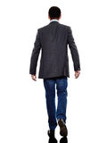 Business man walking rear view silhouette. One caucasian business man walking rear view in silhouette on white background royalty free stock images