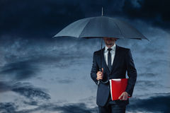 Businessman holding umbrella. Business man walking through stormy weather holding red folder Stock Photography