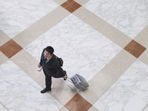 Business man walking with suitcase elevated view. Elevated view of a businessman walking with suitcase on tiled floor Royalty Free Stock Images