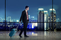 Business man walking with suitcase over city background Royalty Free Stock Image