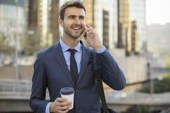 Business man walking talking on cell phone Royalty Free Stock Image