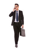 Business man walking and talking on phone. Young business man walking and talking on phone while looking to a side on white background Royalty Free Stock Photos