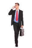 Business man Walking and talking on phone. Business man Walking forward and looking to a side while talking on the phone and carying a briefcase over white Royalty Free Stock Image