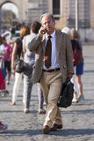Business man walking and talking on the phone Royalty Free Stock Photo