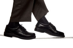 Business man walking a tight rope Royalty Free Stock Photography