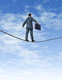 Business man Walking A Tightrope. Business man with a briefcase walking a dangerous high risk tightrope as a financial symbol of trust and confidence with Stock Photo