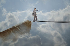 Business man walking a tightrope. Business man walking a dangerous high risk tightrope as a financial symbol of trust and confidence with courage and reliability Stock Photography