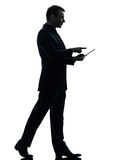 Business man walking touchscreen digital tablet  silhouette Stock Photos